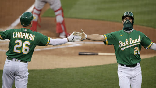 Oakland Athletics' Mark Canha, right, celebrates with Matt Chapman (26) after both scored against the Los Angeles Angels in the first inning of a baseball game Friday, Aug. 21, 2020, in Oakland, Calif. Both scored on a double by A's Stephen Piscotty. (AP Photo/Ben Margot)