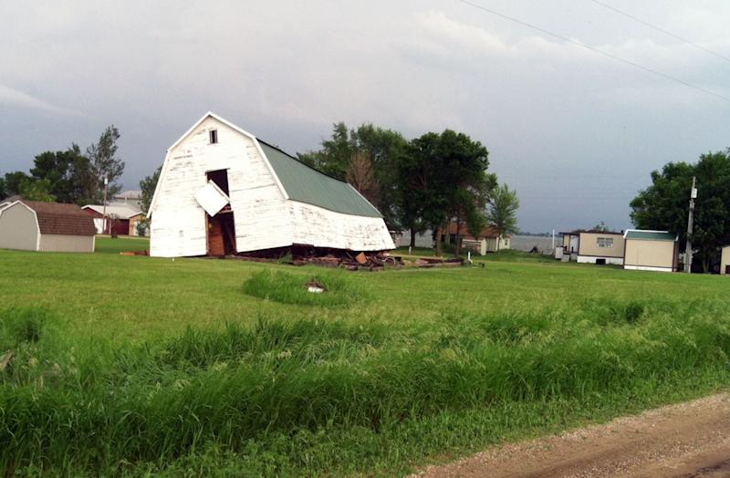 A barn slides off its foundation after a fast-moving line of strong storms that barreled across northeast South Dakota spawned several tornadoes, Friday, June 21, 2013, at Lake Poinsett, S.D. One woman was killed when her trailer was tossed in the air from the storms. (AP Photo/Tena Haraldson)