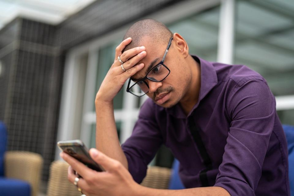 Businessman worried about the news on his mobile phone
