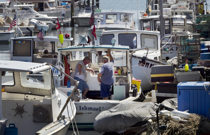 Lobstermen take a break while doing maintenance work, Thursday, August 9, 2012, in Portland, Maine. Plentiful lobsters this season has depressed the prices that lobstermen have been getting, to below $3 a pound. In recent weeks Maine lobstermen stayed off the water for several days to try to let the market rebound. (AP Photo/Robert F. Bukaty)