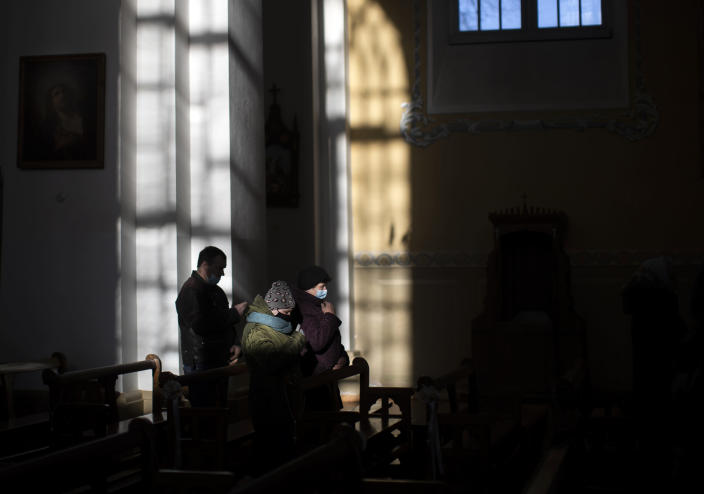 Worshippers wearing face masks to prevent the spread of the coronavirus, pray during the Easter vigil Mass at the St. Trinity Church in a small town Tverecius, some 135km (83.1 miles) northeast of the capital Vilnius, Lithuania, on Saturday, April 3, 2021. (AP Photo/Mindaugas Kulbis)