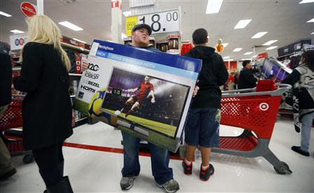 A holiday shopper carries a discounted television to the checkout at the Target retail store in Chicago, Illinois, in this file photo taken November 28, 2013. REUTERS/Jeff Haynes/Files
