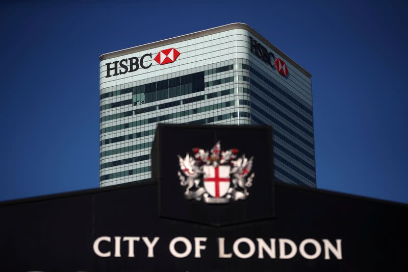 FILE PHOTO: HSBC's building in Canary Wharf is seen behind a City of London sign outside Billingsgate Market in London