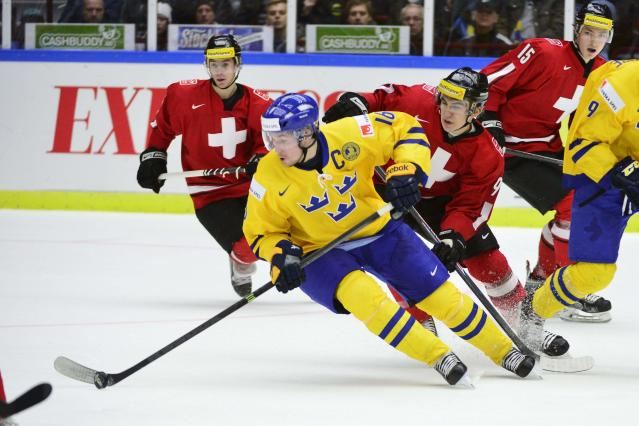 Sweden's Filip Forsberg is chased by Switzerland's Samuel Kreis during their IIHF World Junior Hockey Championship ice hockey game in Malmo December 26, 2013. REUTERS/Ludvig Thunman/TT News Agency (SWEDEN - Tags: SPORT ICE HOCKEY) ATTENTION EDITORS - THIS IMAGE WAS PROVIDED BY A THIRD PARTY. THIS PICTURE IS DISTRIBUTED EXACTLY AS RECEIVED BY REUTERS, AS A SERVICE TO CLIENTS. SWEDEN OUT. NO COMMERCIAL OR EDITORIAL SALES IN SWEDEN. NO COMMERCIAL SALES