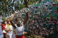 Demonstrators dance in an alley adorned with pinwheels that represent people who have died of COVID-19 during a memorial event in Sao Paulo, Brazil, Wednesday, Oct. 6, 2021. Infection rates and death counts are down in the country, but Brazil will hit 600,000 pandemic deaths in the coming days. (AP Photo/Andre Penner)