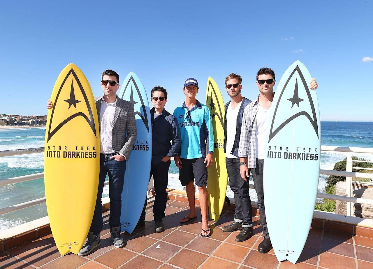 "SYDNEY, AUSTRALIA - APRIL 22:  Zachary Quinto, J.J. Abrams, Lifeguard Dean ""Deano"" Gladstone, Chris Pine and Karl Urban pose at Bondi Beach at the ""Star Trek Into Darkness"" photo call on April 22, 2013 in Sydney, Australia.  (Photo by Marianna Massey/Getty Images for Paramount Pictures International)"