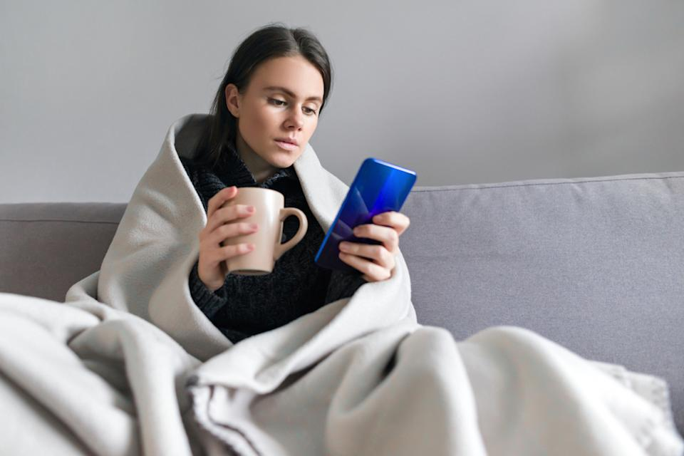 young woman wrapped in blanket with mug, looking at phone
