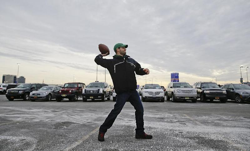 Matt Ciccone throws a football in the parking lot near MetLife Stadium before the NFL Super Bowl XLVIII football game between the Seattle Seahawks and the Denver Broncos Sunday, Feb. 2, 2014, in East Rutherford, N.J. (AP Photo/Seth Wenig)