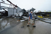Steven Voisin walks past some of the destruction of his oyster processing plant, in the aftermath of Hurricane Ida in Houma, La., Tuesday, Sept. 14, 2021. Voisin said he has yet to compute a dollar estimate for damage to the company, which also operates boats that harvest oysters, but it's substantial. (AP Photo/Gerald Herbert)