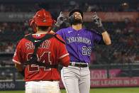 Colorado Rockies' Sam Hilliard, right, gestures as he scores after hitting a three-run home run as Los Angeles Angels catcher Kurt Suzuki stands at the plate during the fourth inning of a baseball game Tuesday, July 27, 2021, in Anaheim, Calif. (AP Photo/Mark J. Terrill)