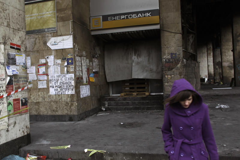 A woman walks past a local bank set on fire in Kiev's Independence Square, the epicenter of the country's current unrest, Ukraine, Tuesday, Feb. 25, 2014. Ukraine needs money, and fast _ in weeks, not months. But bailing out the country of 46 million people will not be as easy as simply writing a big check. For one, Ukraine has already burned the main international financial rescuer, the International Monetary Fund, by failing to keep to the terms of earlier bailouts from 2008 and 2010. Now it needs help again, and its economic and financial problems are worse than before. (AP Photo/Marko Drobnjakovic)