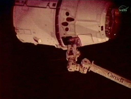 In this frame grab from a NASA video, the robotic arm (bottom) of the International Space Station captures the SpaceX Dragon capsule. The successful maneuver makes SpaceX the first private company to rendezvous with the orbiting lab