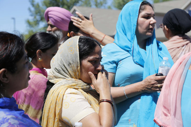FOR USE AS DESIRED WITH SIKH TEMPLE SHOOTING ANNIVERSARY STORIES - FILE - In this Aug. 5, 2012, file photo bystanders stand outside the scene of a shooting at the Milwaukee-area Sikh temple in Oak Creek, Wis. Twelve months ago, a white supremacist walked into a the temple and opened fire on worshippers he didn't know, killing six and devastating a Sikh community whose religion is based on peace and forgiveness. Monday is the one-year anniversary of the shooting. (AP Photo/Jeffrey Phelps, File)