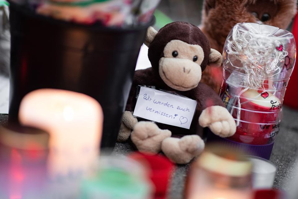 """dpatop - 02 January 2020, North Rhine-Westphalia, Krefeld: """"We'll miss you!"""" is written on a slip of paper stuck to a stuffed monkey. Numerous pictures, stuffed animals and candles are lying in front of the main entrance of the Krefeld Zoo. After the fire in the monkey house with many dead animals, there are, according to investigators, indications of so-called Chinese sky lanterns as the cause of the fire. Photo: Marcel Kusch/dpa (Photo by Marcel Kusch/picture alliance via Getty Images)"""