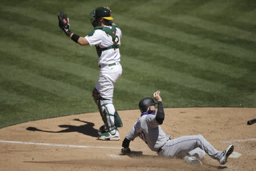 Colorado Rockies' Trevor Story, right, scores past Oakland Athletics catcher Sean Murphy (12) during the eighth inning of a baseball game, Wednesday, July 29, 2020, in Oakland, Calif. (AP Photo/Ben Margot)