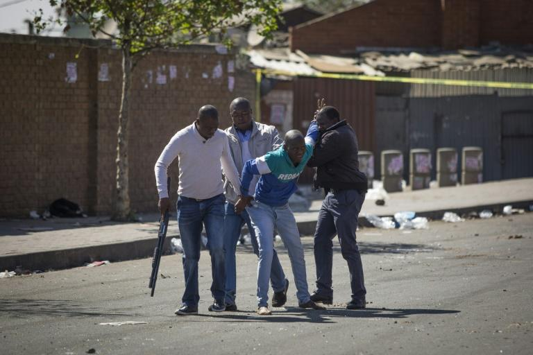 South African police officers detained looters after the outbreak of rioting in the Johannesburg township of Alexandra