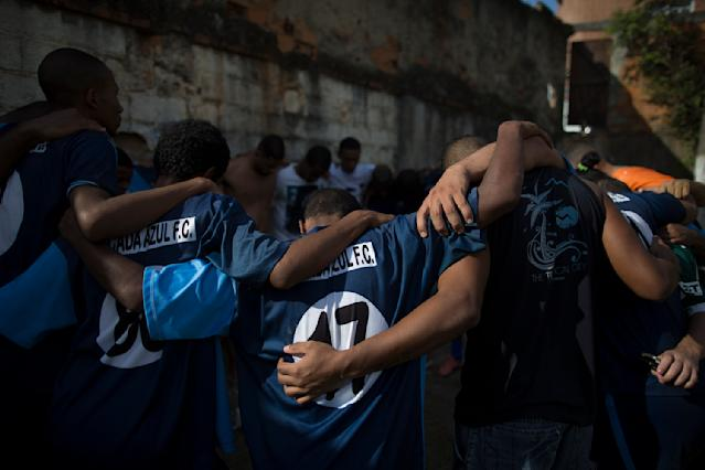 In this May 3, 2014 photo, Escada Azul players pray after their amateur soccer match in the Mangueira shantytown of Rio de Janeiro, Brazil. Brazil is a five-time champion of the World Cup, and will host this year's international soccer tournament starting June. 12. (AP Photo/Leo Correa)