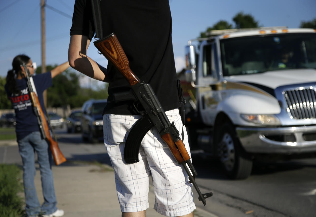 "FILE - In this May 29, 2014, file photo, Kory Watkins, front, coordinator for Open Carry Tarrant County, carries his Romanian AK 47 over his shoulder as he and his wife Janie, rear, along with others, gather for a demonstration in Haltom City, Texas. Companies, customers and others critical of Texas gun rights advocates who have brought military-style assault rifles into businesses as part of demonstrations supporting ""open carry"" gun rights now have a surprising ally: the National Rifle Association. The NRA has long been a zealous advocate for gun owners' rights. But the group's lobbying arm, the Institute for Legislative Action, has called the demonstrations counterproductive to promoting gun rights, scary and ""downright weird."" (AP Photo/Tony Gutierrez, File)"