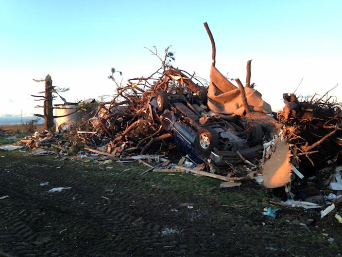 An overturned car rests on top of tree branches and other rubble near the destroyed home of Curt Zehr about a mile northeast of Washington, Ill., on Sunday, Nov. 17. Intense thunderstorms spawning tornadoes swept across the Midwest on Sunday. (AP Photo/David Mercer)