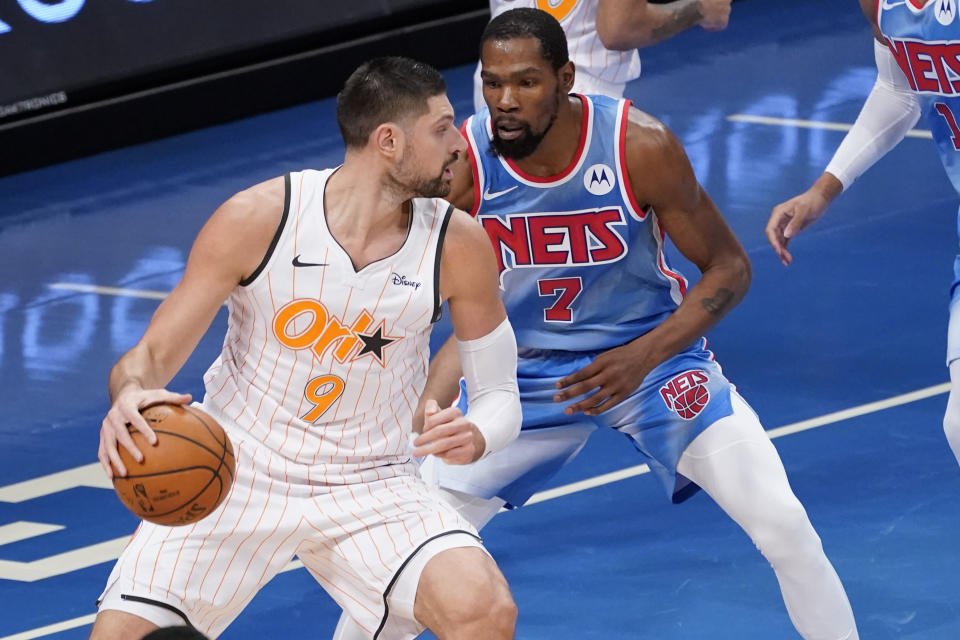 Orlando Magic center Nikola Vucevic (9) drives against Brooklyn Nets forward Kevin Durant (7) during the first half of an NBA basketball game, Saturday, Jan. 16, 2021, in New York. (AP Photo/Mary Altaffer)