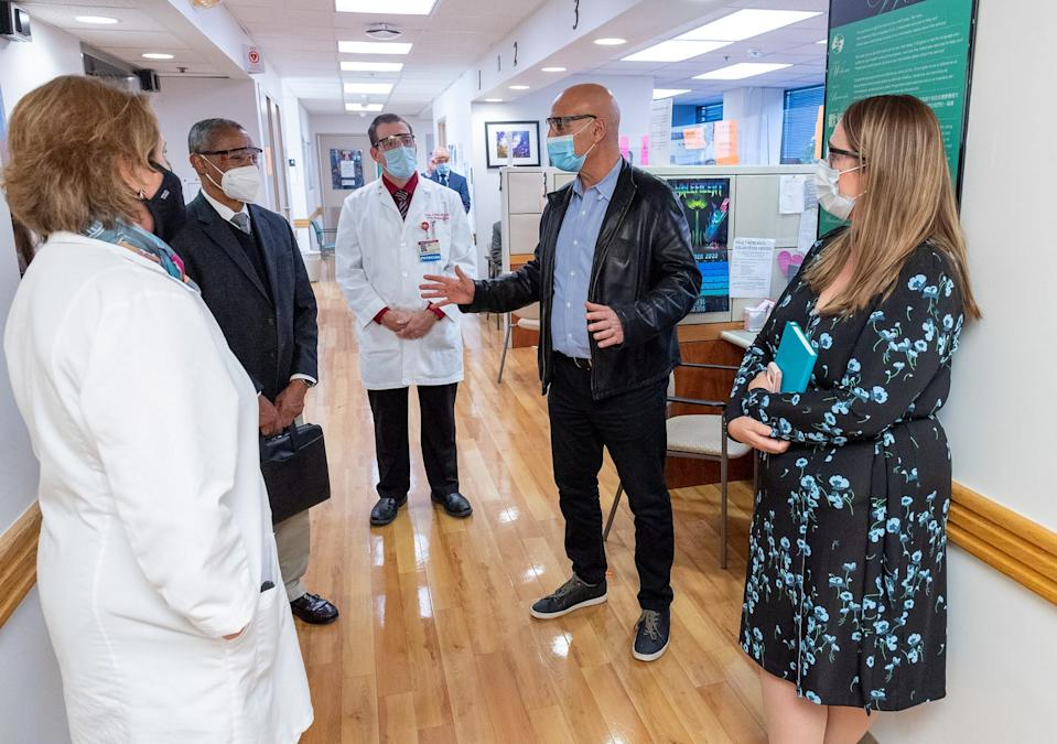 Moncef Slaoui, in leather jacket, tours Temple University Hospital on Nov. 20. Getting a diverse group of clinical trial participants has been  part of his work helping to lead the U.S. COVID-19 vaccine effort.
