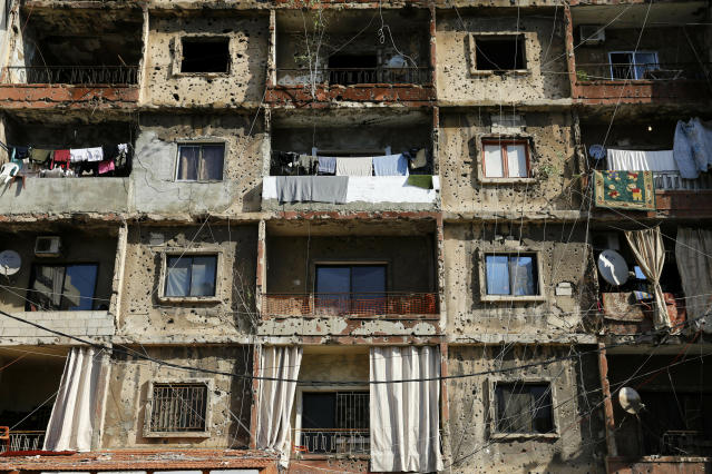 In this Nov. 17, 2018, photo, an inhabited building that is still riddled with bullets and shells left over from the 1975-1990 Lebanese civil war on a former Beirut frontline between Shiyah, a Muslim Shiite district and Christian district of Ain el-Rummaneh, in Beirut, Lebanon. The two sides fought fierce battles during the 1975-90 civil war, which started with a shooting on a bus in Ain el-Rummaneh. (AP Photo/Hassan Ammar)