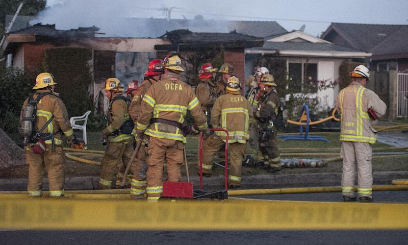 Orange County Fire Authority firefighters survey the damage of a house fire on Wednesday, Jan. 8, 2014 in Santa Ana, Calif. Authorities say two people have been killed and four others injured in the early morning fire at a group home for developmentally disabled adult women. Orange County Fire Authority spokesman Steve Concialdi says the blaze broke out at about 5:45 a.m. Wednesday in the residential neighborhood of Santa Ana. Concialdi says the home's caretaker, a 71-year-old woman, was critically injured while attempting to rescue residents from the single-story, four-bedroom home. (AP Photo/The Orange County Register, Bruce Chambers) MAGS OUT; LOS ANGELES TIMES OUT