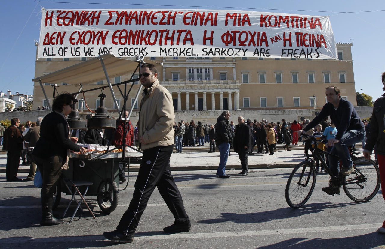 A cyclist and a street vendor are seen under a banner which reads ''National consensus is a trick, poverty and hunger have no nationality'' during a peaceful protest outside the Greek Parliament in Athens, Sunday, Feb. 19, 2012. Tensions between Athens and other European capitals hit new highs this week as eurozone ministers delayed to next Monday a decision on a bailout agreement and demanded more commitments from Greece. (AP Photo/Thanassis Stavrakis)