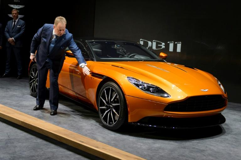 Aston Martin CEO Andy Palmer shows the new DB11 model car during the press day of the Geneva Motor Show on March 1, 2016