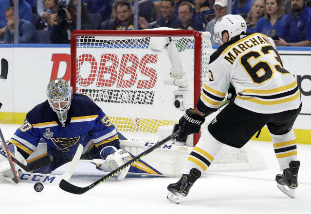 Boston Bruins left wing Brad Marchand (63) reaches for a rebound in front of St. Louis Blues goaltender Jordan Binnington (50) during the first period of Game 6 of the NHL hockey Stanley Cup Final Sunday, June 9, 2019, in St. Louis. (AP Photo/Jeff Roberson)