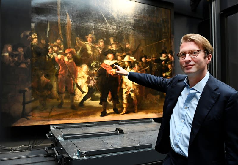 Museum director Taco Dibbits points to Rembrandt's famed Night Watch at Rijksmuseum in Amsterdam