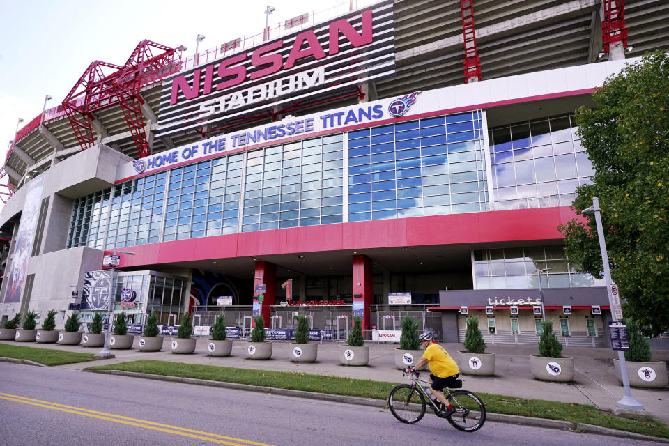 A cyclist passes by Nissan Stadium, home of the Tennessee Titans, Tuesday, Sept. 29, 2020, in Nashville, Tenn. The Titans suspended in-person activities through Friday after the NFL says three Titans players and five personnel tested positive for the coronavirus, becoming the first COVID-19 outbreak of the NFL season in Week 4. (AP Photo/Mark Humphrey)