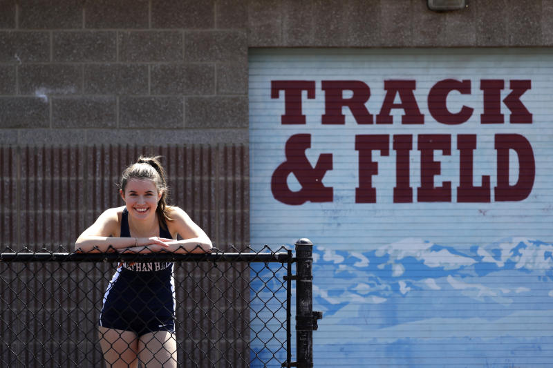 """Nathan Hale High School senior Fran Shannon poses for a photo at her school track, where she was co-captain of the team in Seattle on April 25, 2020. Fran had hoped compete in the triple jump at the Washington state track championships, but that and other dreams were cut short by the coronavirus outbreak. """"Even with all of the things I'm missing out on, I still feel very blessed to have a roof over my head, and food to eat, and access to materials for online classes,"""" says Fran, whose father is a doctor who's helped treat coronavirus patients. She also helped care for her mom, who likely had the virus and was in quarantine for many days. """"There are people who have it a lot worse than I do and I think that's important to keep in mind."""" (AP Photo/Elaine Thompson)"""