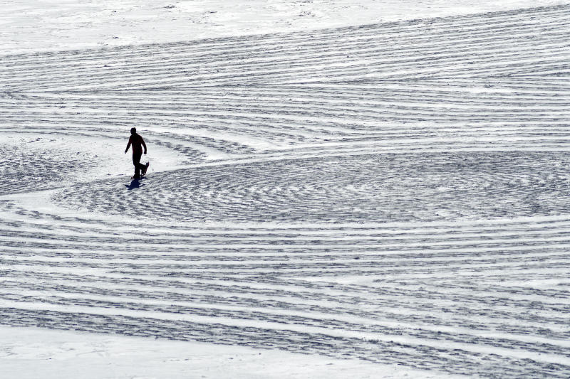 In this photo taken Jan. 7, 2020, British artist Simon Beck uses snowshoes to create a massive geometrical design on a reservoir near Silverthorne, Colo. The 61-year-old has completed about 330 snow drawings and 120 in sand since he started the art form outside his winter home at a French ski resort in 2004. He says he hopes his drawings bring awareness to the beauty of the environment. (AP Photo/Thomas Peipert)