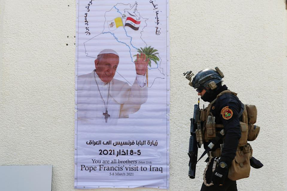 A security man walks near a poster of Pope Francis upon his upcoming visit to Iraq, in Baghdad (REUTERS)