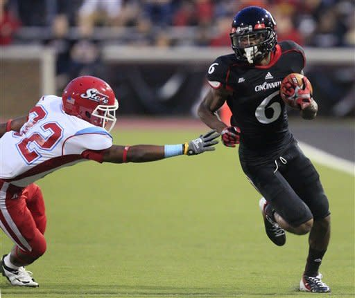 Cincinnati wide receiver Anthony McClung (6) avoids a tackle by Delaware State defensive back Cameren Judge in the first half of an NCAA college football game, Saturday, Sept. 15, 2012, in Cincinnati. (AP Photo/Al Behrman)