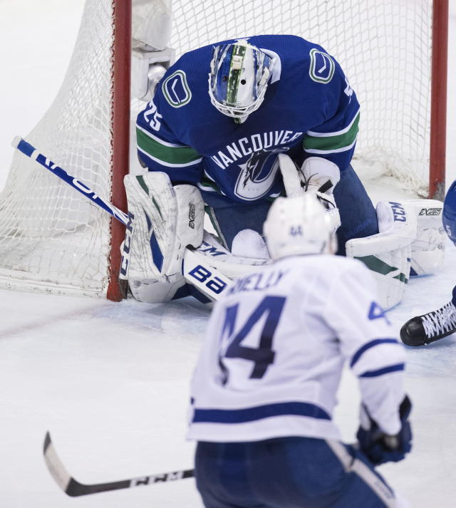 Toronto Maple Leafs' Morgan Rielly, bottom, scores against Vancouver Canucks goalie Jacob Markstrom, of Sweden, during the second period of an NHL hockey game Wednesday, March 6, 2019, in Vancouver, British Columbia. (Darryl Dyck/The Canadian Press via AP)