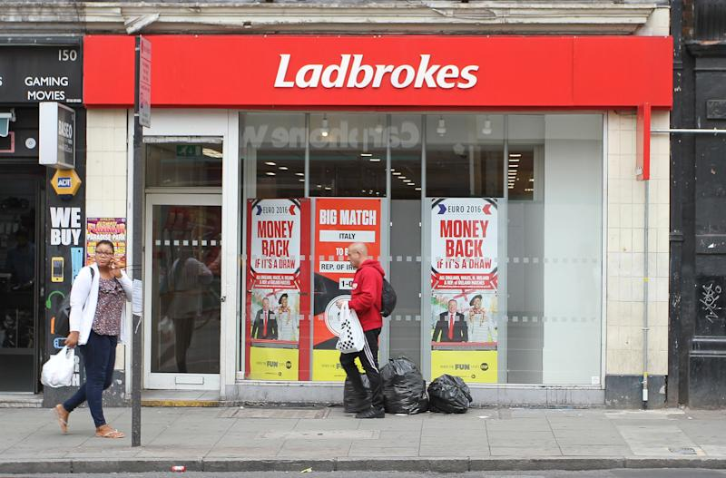 People walk past a Ladbrokes betting shop in London, Wednesday June 22, 2016. Thursday's referendum on whether to leave the European Union, which could have lasting consequences for the country and Europe, is due to break the record as the most bet-upon political event in Britain's history. (AP Photo/Leonora Beck)