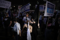Israelis wear face masks wave placards and Israel's national flags during a rally marking 25 years since the assassination of the late Israeli Prime Minister Yitzhak Rabin, at Rabin Square, in Tel Aviv, Israel, Saturday, Nov. 7, 2020. (AP Photo/Sebastian Scheiner)
