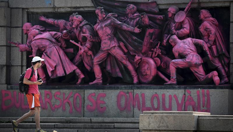 "A person walks past a Soviet Army monument colored pink by unknown people to mark the anniversary of the Prague Spring with an inscription in Bulgarian and Czech below reading ""Bulgaria apologizes."" in Sofia, Wednesday, Aug. 21, 2013. Bulgaria, which marched in lock step with the Soviet Union for decades, was the first country to insist on the invasion and the last one to formally apologize for its participation – with a declaration of Parliament in 1990, and in 1997, during a presidential visit to Prague. (AP Photo/Valentina Petrova)"