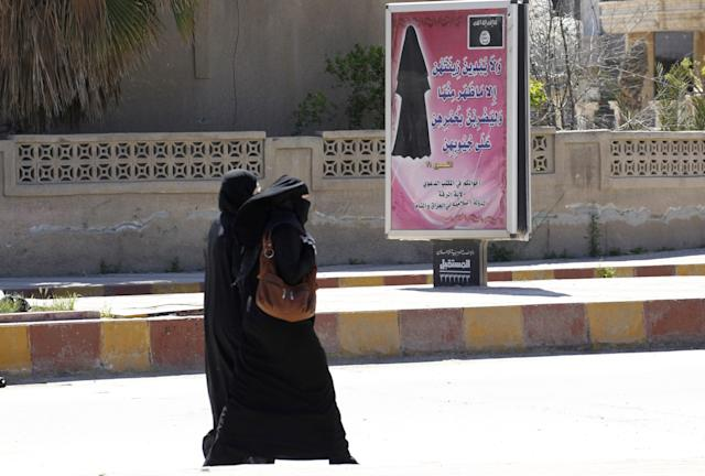 Veiled women walk past a billboard that carries a verse from Koran urging women to wear a hijab in the northern province of Raqqa