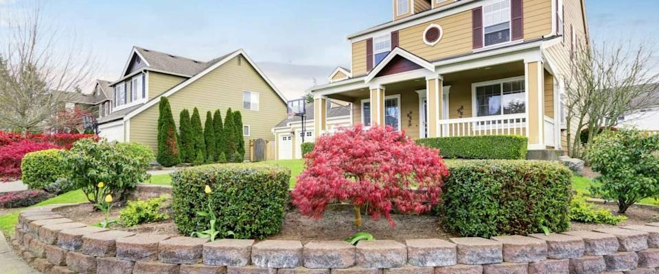 American house exterior with covered porch and columns. Beautiful curb appeal and perfect landscape design. Northwest, USA