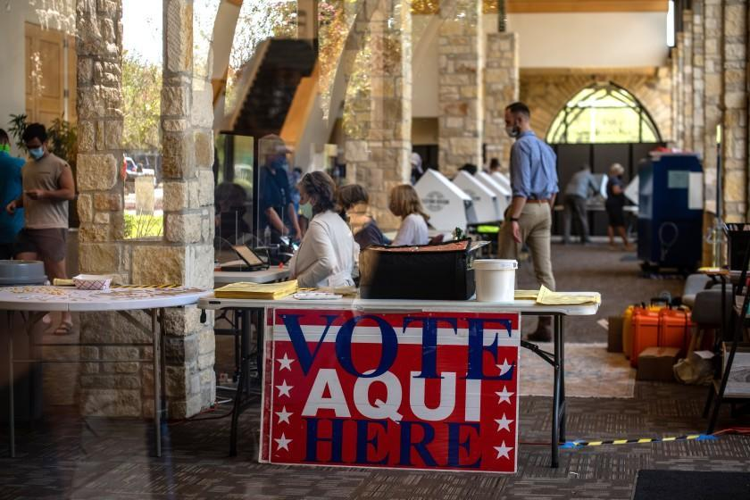 AUSTIN, TX - OCTOBER 13: Poll workers help voters inside a polling location on October 13, 2020 in Austin, Texas. The first day of voting saw voters waiting hours in line to cast their votes. Gov. Greg Abbott announced earlier this year that he would expand early voting for the election beginning on Oct. 13. Mail in voting began on Oct. 8 and has been part of a legal battle after Gov. Abbott declared each county may only have 1 mail in ballot drop off center, the ruling was later struck down in federal court but then the decision was upheld when a stay was ruled in the overturning. (Photo by Sergio Flores/Getty Images)