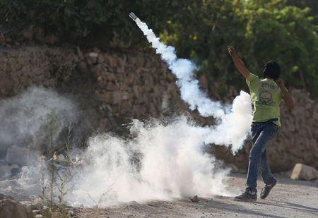A Palestinian protester returns a tear gas canister fired by Israeli troops during clashes following the funeral of Palestinian youth Laith al-Khaldi, in Jalazoun refugee camp near the West Bank city of Ramallah August 1, 2015. REUTERS/Mohamad Torokman