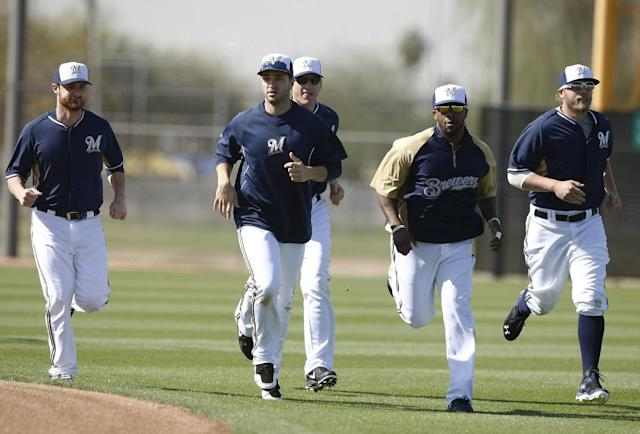 Milwaukee Brewers' Ryan Braun, second from left, and Rickie Weeks (23) lead running drills during baseball spring training Saturday, Feb. 22, 2014, in Phoenix