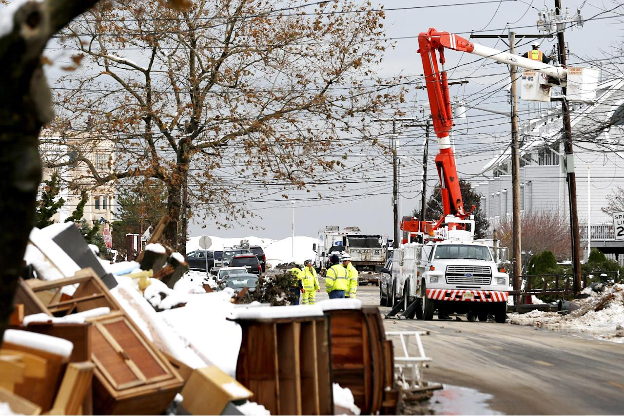 Utility workers the the power lines as snow covered debris from Superstorm Sandy lay on the side of a street following a nor'easter storm, Thursday, Nov. 8, 2012, in Point Pleasant, N.J. The New York-New Jersey region woke up to wet snow and more power outages Thursday after the nor'easter pushed back efforts to recover from Superstorm Sandy, that left millions powerless and dozens dead last week. (AP Photo/Julio Cortez)