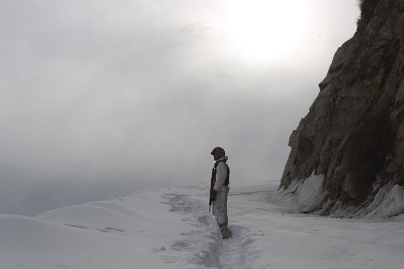 In this Friday, Feb. 17, 2012 photo, a Pakistani Army soldier with the 20th Lancers Armored Regiment, stands on the 8000-foot mountain near his outpost, Kalpani Base, in Pakistan's Dir province on the Pakistan-Afghan border. Kalpani is on the front line in the 10-year war against militant Islamists, a war which allies Pakistan with the U.S. and NATO in an uneasy, distrustful partnership. Pakistan feels scapegoated for the coalition's failures in Afghanistan. At the same time it's accused of playing a double game, fighting the militants it chooses to fight while giving others safe havens and logistical support for their actions in Afghanistan. (AP Photo/Anja Niedringhaus)