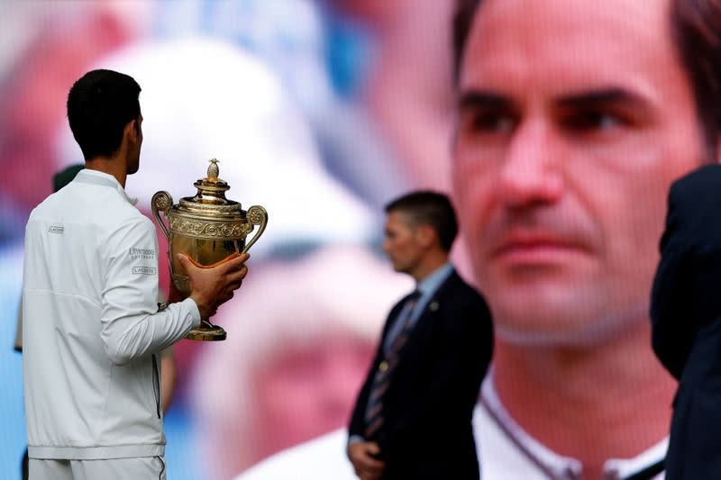FILE PHOTO: Serbia's Novak Djokovic holds the Wimbledon trophy after winning the 2019 final as Switzerland's Roger Federer is on a screen in the background Wimbledon