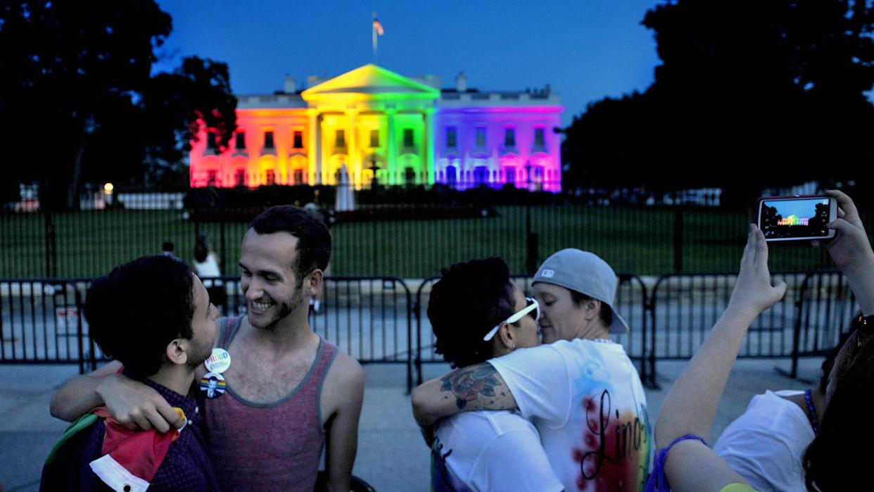 WASHINGTON, DC- JUNE 26: With at colorful White House backdrop, (L) Kevin Barragan and his partner Adam Smith celebrate the decision today as do Kelly Miller (with glasses) and her wife Lindsey Miller. The Miller's were married 2 years ago in Washington State where gay marriage was legal.The White House was lit in multi-colored lights tonight to honor the Supreme Court decision to allow gay marriage. Michael S. Williamson/The Washington Post via Getty Images)