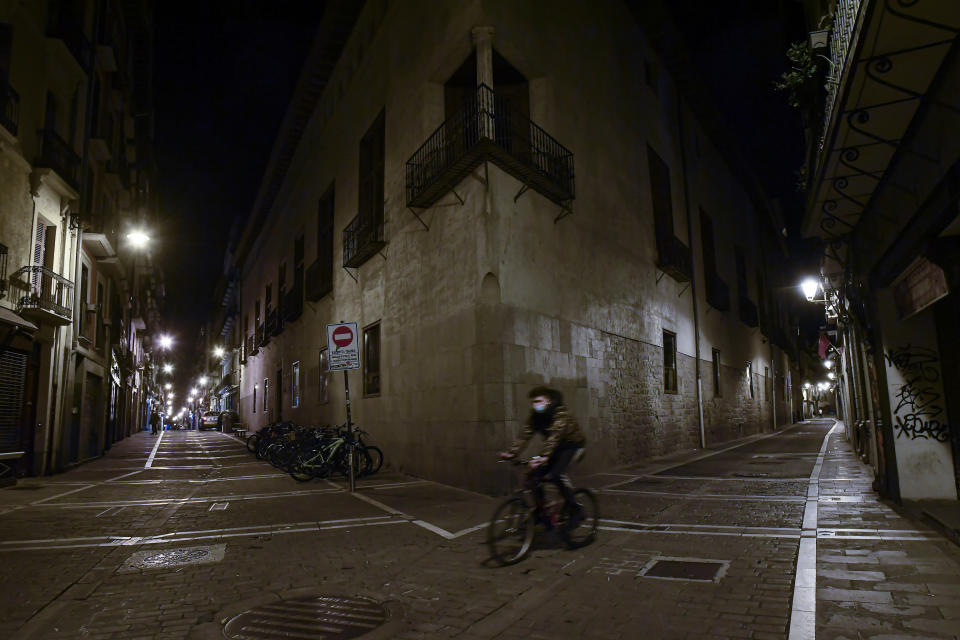 A cyclist wearing face mask protection crosses along an empty High street, in Pamplona, northern Spain, Saturday, Oct. 24, 2020, as new measures against the coronavirus began in the Navarra province where all bar and restaurants are closed for 15 days from midnight Wednesday. (AP Photo/Alvaro Barrientos)